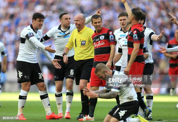 Match referee Lee Mason is surrounded by players after Derby County's Johnny Russell is fouled by Queens Park Rangers' Gary O'Neil