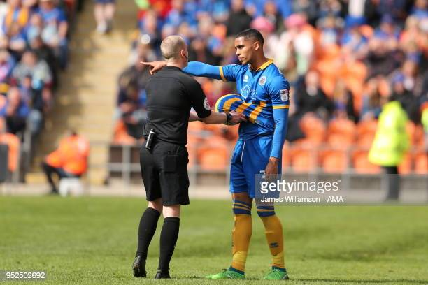 Match referee Martin Coy retreives the match ball from under the shirt of Max Lowe of Shrewbury Town during the Sky Bet League One match between...