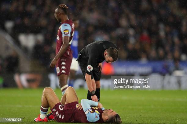 Match referee Michael Oliver in discussion with a downed Jack Grealish of Aston Villa during the Premier League match between Leicester City and...