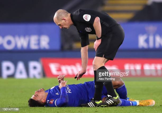 Match Referee, Mike Dean checks on James Justin of Leicester City who looks to be injured during The Emirates FA Cup Fifth Round match between...