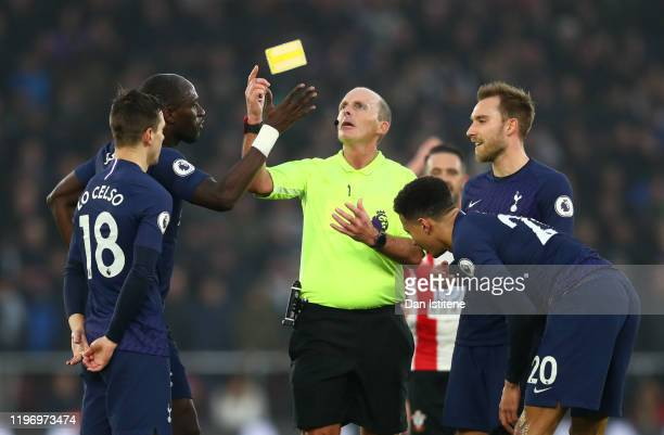 Match Referee Mike Dean drops his yellow card as he speaks to Giovani Lo Celso of Tottenham Hotspur during the Premier League match between...