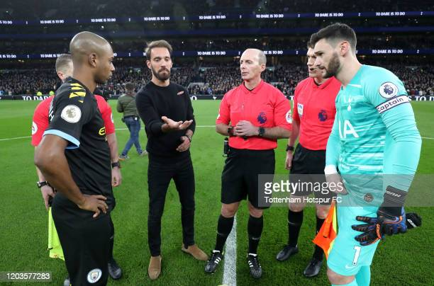 Match Referee Mike Dean, Fernandinho and Hugo Lloris of Tottenham Hotspur look on during the coin toss prior to the Premier League match between...