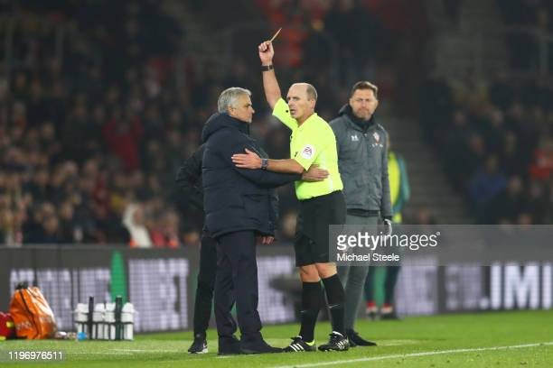 Match Referee Mike Dean shows a yellow card to Jose Mourinho Manager of Tottenham Hotspur during the Premier League match between Southampton FC and...