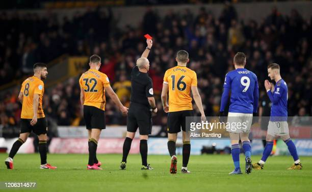 Match Referee Mike Dean shows Hamza Choudhury of Leicester City the red card during the Premier League match between Wolverhampton Wanderers and...