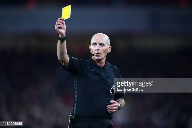 Match Referee Mike Dean shows the Yellow card during the Premier League match between Sheffield United and Arsenal FC at Bramall Lane on October 21,...