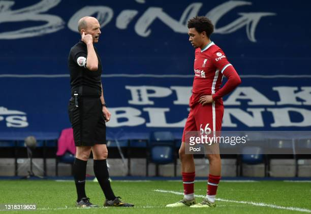 Match Referee, Mike Dean waits with Trent Alexander-Arnold of Liverpool for a VAR decision on an offside goal scored by Kyle Bartley of West Bromwich...