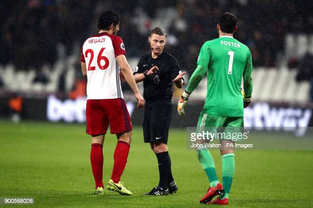 Match referee Mike Jones talks to West Bromwich Albion's Ahmed Hegazy and Ben Foster at half time during the Premier League match at London Stadium