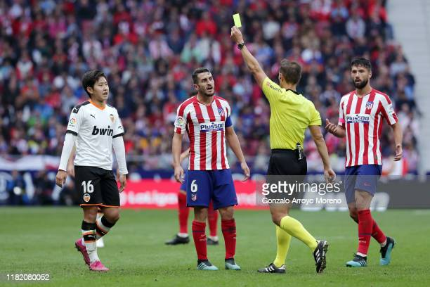 Match referee shows a yellow card to Lee Kang-In of Valencia during the Liga match between Club Atletico de Madrid and Valencia CF at Wanda...