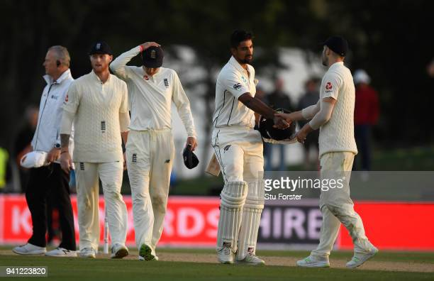 Match saving batsman Ish Sodhi shakes hands with Mark Wood as England captain Joe Root reacts as the match finishes as a draw during day five of the...