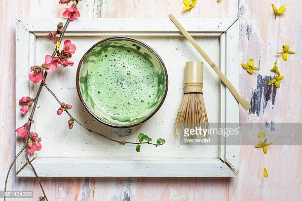 Matcha tea in bowl, with match powder, spoon and chasen and pink flowers