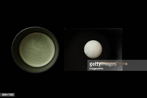 Matcha (Japanese powdered green tea)   with cake against black background, close-up