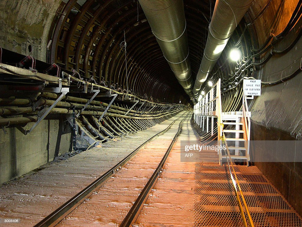 This undated image obtained 22 February, 2004 shows a rail tunnel descending into the Yucca Mountain nuclear waste repository located in Nye County, Nevada, about 100 miles northwest of Las Vegas. Yucca Mountain is the US Department of Energy's potential geologic repository designed to store and dispose of spent nuclear fuel and high-level radioactive waste. By the year 2010, If all licenses are granted, the facility will begin receiving casks of spent atomic fuel from aircraft carriers, submarines and power plants and will eventually become the largest repository of nuclear waste in the world. The eight-kilometer (five-mile) long underground gallery has 12 alcoves dug out along its length that serve as laboratories. Here, rock is measured for consistency and water content, heated and frozen, and every crack is closely watched. A 60-to-80-kilometer (40-to-50 mile) long grid of tunnels will be excavated through Yucca Mountain's core to house hermetically sealed containers holding up to 77,000 tons of deadly waste.