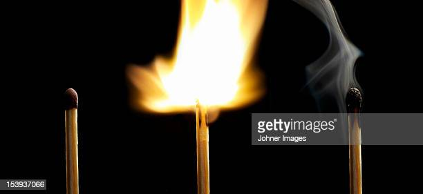 matchstick burning on black background - burnout stock photos and pictures