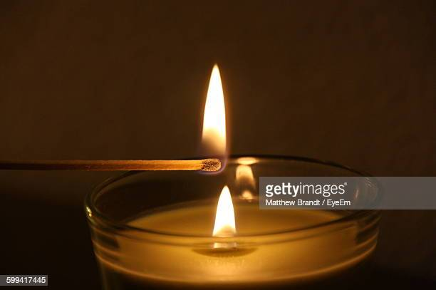 matchstick lighting candle over plain background - match lighting equipment stock photos and pictures