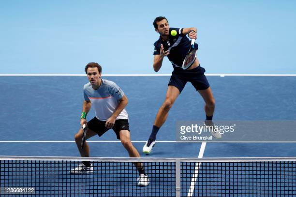 Mate Pavic of Croatia plays a volley playing with partner Bruno Soares of Brazil during their doubles match against Michael Venus of New Zealand and...