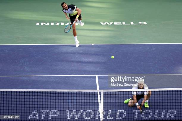 Mate Pavic of Croatia serves to returns a shot to John Isner and Jack Sock while playing with Oliver Marach of Austria during the doubles semifinals...