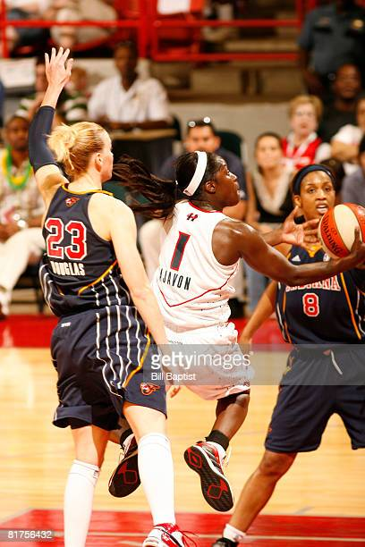 Matee Ajavon of the Houston Comets shoots the ball over Katie Douglas and Tammy Sutton-Brown of the Indiana Fever at Reliant Arena on June 28, 2008...