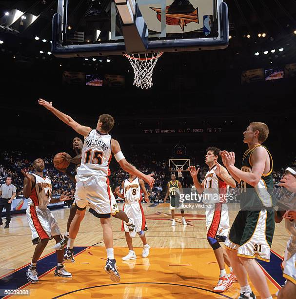 Mateen Cleaves of the Seattle Sonics battles for a shot against Andris Biedrins of the Golden State Warriors during a preseason game at The Arena in...