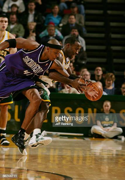 Mateen Cleaves of the Seattle SuperSonics and Bonzi Wells of the Sacramento Kings reach for a loose ball at Key Arena November 20, 2005 in Seattle,...