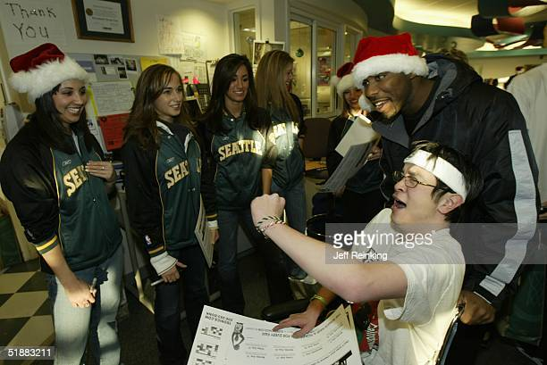 Mateen Cleaves of the Seattle SuperSonics joins patient Luke and the Sonics dance team in a holiday cheer on December 20, 2004 at Childrens Hospital...