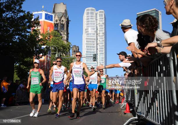 Matej Toth of Slovakia greets a spectator as he competes in the Men's 50km Race Walk final during day one of the 24th European Athletics...