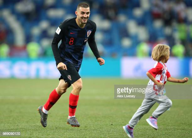Mateo Kovacic of Croatia celebrates with his child following his sides victory in a penalty shoot out during the 2018 FIFA World Cup Russia Round of...