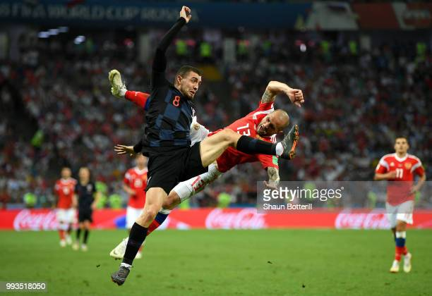 Mateo Kovacic of Croatia clashes with Fedor Kudriashov of Russia during the 2018 FIFA World Cup Russia Quarter Final match between Russia and Croatia...