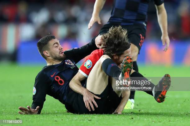 Mateo Kovacic of Croatia pulls Joe Allen of Wales down on his knee as he tackles him during the UEFA Euro 2020 qualifier between Wales and Croatia at...