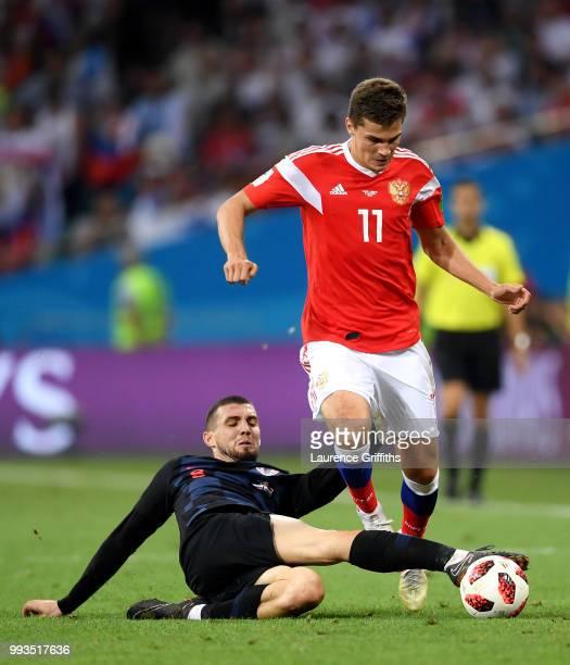 Mateo Kovacic of Croatia tackles Roman Zobnin of Russia during the 2018 FIFA World Cup Russia Quarter Final match between Russia and Croatia at Fisht...