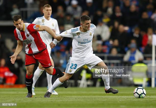 Mateo Kovacic of Real Madrid competes for the ball with Alex Granell of Girona during the La Liga match between Real Madrid and Girona at Estadio...