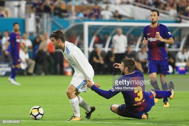 Mateo Kovacic of Real Madrid gets past Gerard Pique of Barcelona on his way to scoring a goal in the first half against the Barcelona during their...