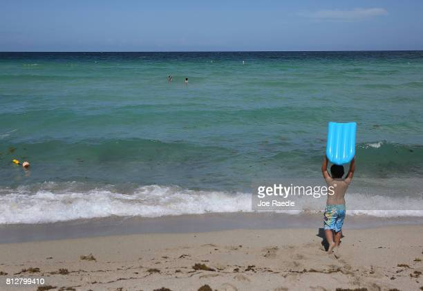 Mateo Saez prepares to enter the ocean water off of Haulover Beach where a rare shark attack occured on Sunday afternoon on July 11 2017 in Sunny...