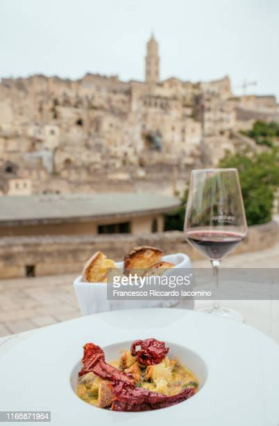 matera, typical food plate with peperoni cruschi and town in background - iacomino italy foto e immagini stock