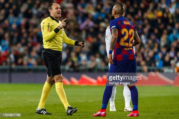Mateu Lahoz referee gestures and Arturo Vidal of FC Barcelona looks on during the Liga match between Real Madrid CF and FC Barcelona at Estadio...