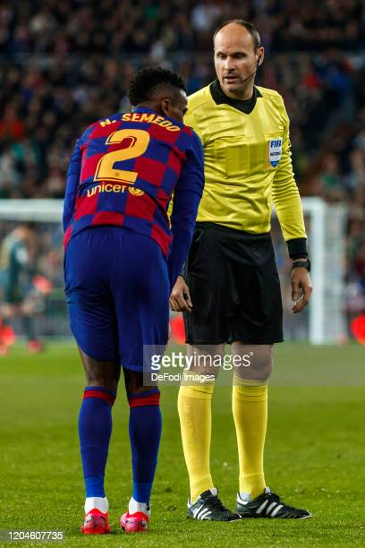 Mateu Lahoz referee looks on and Nelson Semedo of FC Barcelona looks dejected during the Liga match between Real Madrid CF and FC Barcelona at...