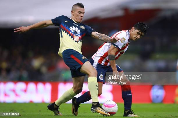Mateus Uribe of America struggles for the ball with Alan Pulido of Chivas during the 10th round match between America and Chivas as part of the...