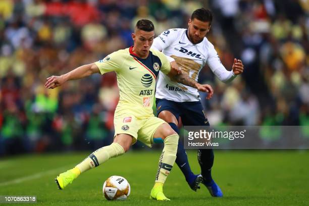 Mateus Uribe of America struggles for the ball with Andres Iniestra of Pumas during the semifinal second leg match between America and Pumas UNAM as...