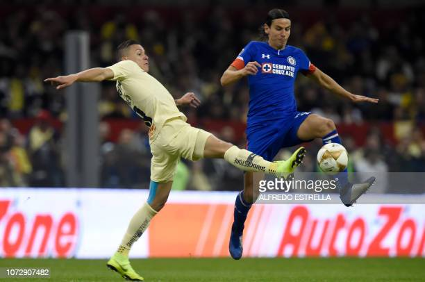 Mateus Uribe of America vies for the ball with Igor Lichnovsky of Cruz Azul during the first round match of the final of the Mexican Apertura...