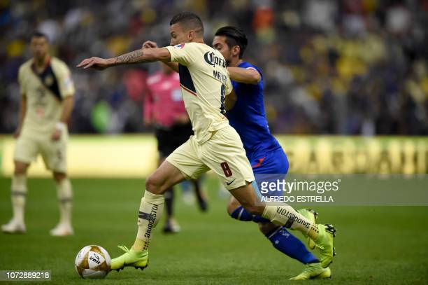 Mateus Uribe of America vies for the ball with Javier Salas of Cruz Azul during the first round match of the final of the Mexican Apertura football...