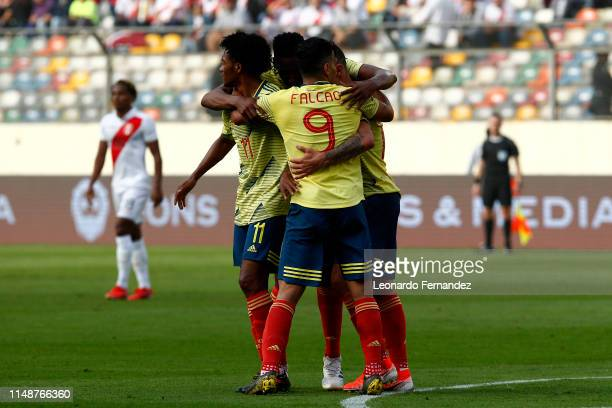 Mateus Uribe of Colombia celebrates with teammates after scoring the first goal of his team during a friendly match between Peru and Colombia at...