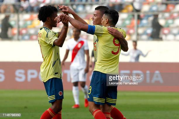 Mateus Uribe of Colombia celebrates with teammates Juan Cuadrado and Radamel Falcao after scoring the first goal of his team during a friendly match...