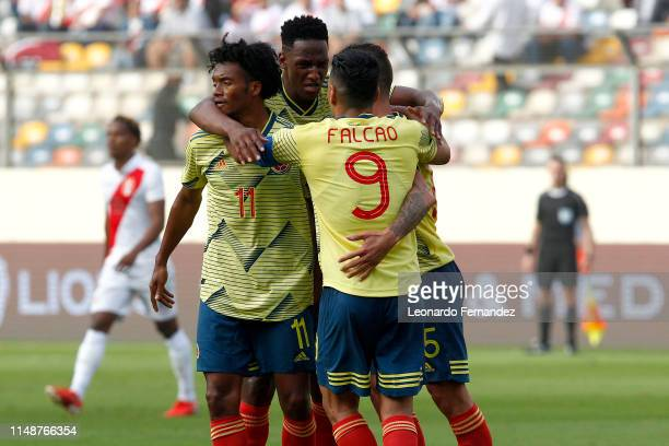 Mateus Uribe of Colombia celebrates with teammates Yerry Mina, Juan Cuadrado and Radamel Falcao after scoring the first goal of his team during a...
