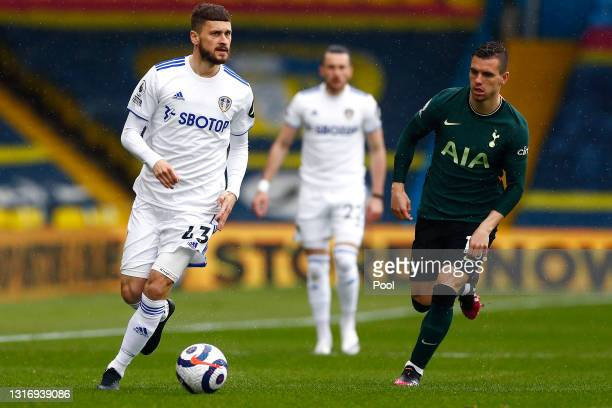Mateusz Klich of Leeds United runs with the ball under pressure from Giovani Lo Celso of Tottenham Hotspur during the Premier League match between...