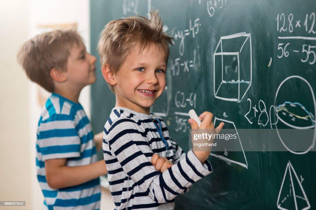 Mathe kann Spaß – Jungen standing an der Tafel : Stock-Foto
