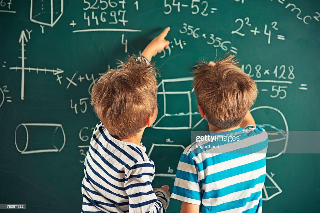 Matematica è divertente-little boys risolvere problemi di matematica : Foto stock