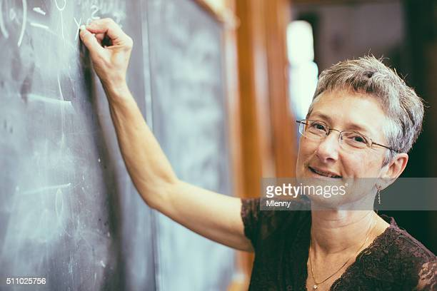 Math teacher at chalkboard writing formula