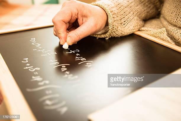 math teacher writing on the blackboard