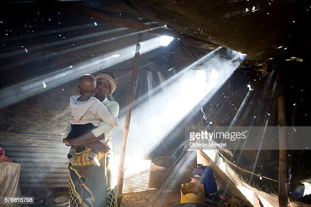 Mathato Notsi with her ten month old baby Mpho in the smoky plastic sheeting shelter which is used as a kitchen at her mother's home Mathato...