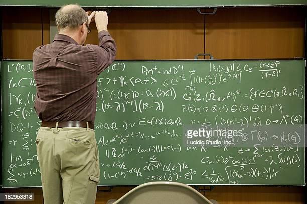 Mathematician working on a blackboard