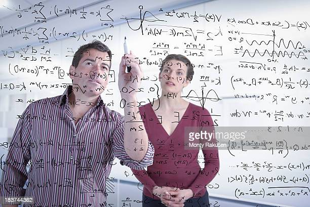 mathematicians writing complex scientific equations on screen - mathematician stock pictures, royalty-free photos & images